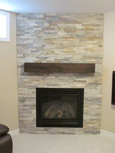 Ledge stone fireplace with rustic, reclaimed  wood mantel.