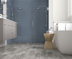 Shower with blue subway tile and an invisible glass shower door and gray wood grain floor tiles.