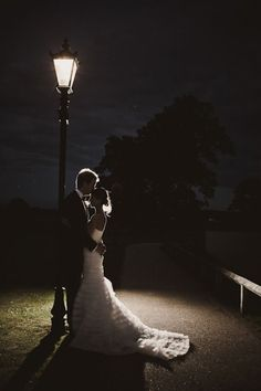 Bride and groom under a street lamp at night beautiful nighttime wedding shot.