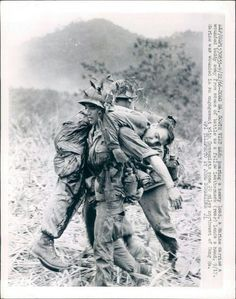 warinvietnam: DONG HA, SOUTH VIET NAM: Bearing a heavy load, a Marine carries a wounded buddy away from scene of battle as a fellow Leatherneck (rear) lends a hand, 9/17. Marine was wounded in an engagement with Communists some 20 miles northwest of Dong Ha.UPI TELEPHOTO BY JOHN SCHNEIDER