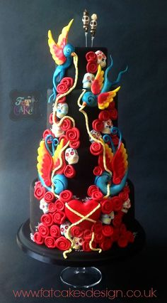 Black wedding cake. Day of the dead skulls, Tattoo swallows, hearts and rope.