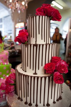 3-tier Wicked chocolate wedding cake iced in white ganache with dark chocolate drizzle, decorated with fresh hot pink roses by Charly's Bakery, via Flickr