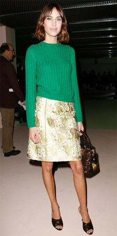 Alexa Chung hit the Prada fall/winter 2015 show during Milan Fashion, grounding a gold brocade skirt with a cheery Kelly green knit and accessorizing with a carryall and black mules.