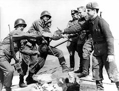 Russian and American soldiers shaking hands and greeting each other as Allies at the end of World War 2.
