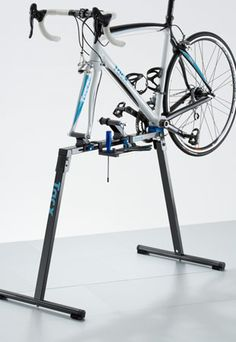 tacx.com - CycleMotion Stand  The CycleMotion stand is a foldable repair stand for heavy-duty repairs and maintenance. It makes repairing and assembling a lot easier. The bicycle is attached to the front or rear fork and rests on the bracket support. Both fork holders are adjustable in height and length. Also handy: the tool tray is removable. You can decide where to attach it while tinkering. Suitable for racing bicycles and MTBs with 5 mm quick release.