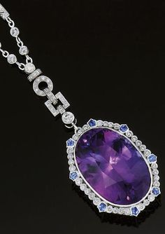 AN AMETHYST, DIAMOND AND SAPPHIRE PENDANT NECKLACE  The central oval amethyst drop with brilliant-cut diamond surround and pentagonal shaped sapphire accents, to a brilliant-cut diamond single stone surmount and diamond articulated panel and collet and bar set twin chain suspension with diamond loop top and belcher link neckchain with matching diamond collet and bar decoration