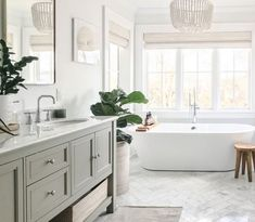 Bathroom featuring herringbone marble floor tile, white beaded chandelier over freestanding tub surrounded by windows dressed in white bamboo Roman shades over bathtub Young House Love, Bad Inspiration, Bathroom Inspiration, Herringbone Marble Floor, Home Luxury, Luxury Interior, Luxury Homes, Bathroom Trends, Bathroom Ideas