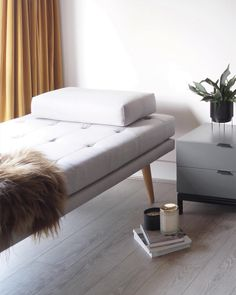 Grey decor with a hint of ochre. Minimal daybed and velvet curtains. 70s home decor with green plants.