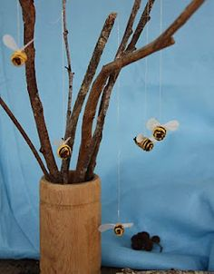 Bees. On sticks. Tiny pine cones, yellow wool, tracing paper and gold thread.