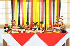 festa com tema mickey para menino de um ano com cortina de fitas de cetim  atrás da mesa do bolo.