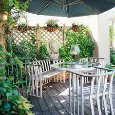 Garden privacy ideas wooden trellis hanging baskets sitting area parasol