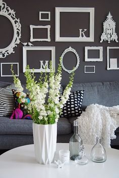 I absolutely love this color combination.  The grey walls and sofa make the empty white frames and gorgeous white flower arrangement really pop! Plus, the empty frames are a unique way to add accents in a room without worrying if the colors in your pictures coordinate.  You can show off really cool frames!