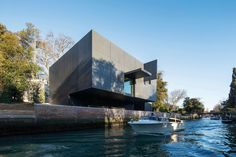 The brooding black box cantilevers over the canal, its recessed ground floor housing service areas and an office.