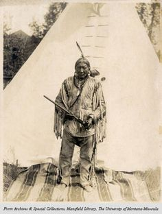 First photograph ever made of Chief Big Rock (77), medicine man of Chippewa Indians, in front of lodge furnished by Charles M. Russell in 1916 on rear of lot of Theodore Gibson's 4th Street and 4th Avenue property, Great Falls, MT. Big Rock gave F. B. Linderman origin and ancient customs, superstitions, traditions and religion of Chippewa which were used as basis of Indian Old-Man Stories, 1920.