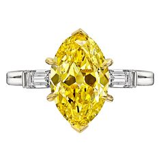Tiffany 2.59 Carat Fancy Vivid Yellow Diamond Gold Platinum Engagement Ring. Diamond engagement ring, centering on a natural fancy vivid yellow diamond weighing 2.59 carats, flanked by two near-colorless baguette-cut diamond shoulders weighing 0.32 total carats (G-H color/VVS1-VVS2 clarity), mounted in platinum with an 18k yellow gold central basket, the setting stamped 'TIFFANY & CO.'