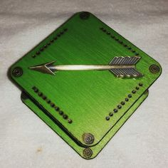 Metallic green box with arrow medallion and burned details