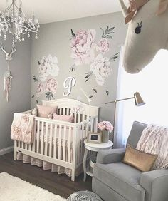This baby girls nursery is so beautiful with so many unique elements. The floral decals on the wall are gorgeous and compliment the chandelier perfectly. That crib and bedding are beautiful and the unicorn is too cute!