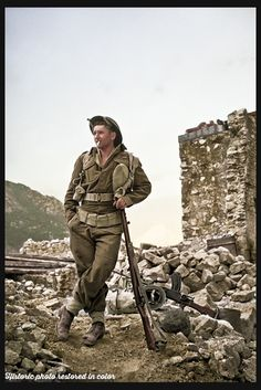 J D Ruscoe (Wanganui) leaning on his rifle, in an informal and characteristic New Zealand pose, on the Cassino battlefront in Italy, 5 April 1944 Photograph taken by George Kaye Coloured by Historic photo restored in color