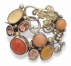 Dorrie Nossiter. An Arts and Crafts brooch, silver with bead and gold leaf motifs, with facetted and cabochon coral, facetted topaz and cabochon citrines. Measures 3.1 cm by 3.2 cm. Sold by Tennants.