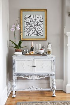 white worn side cabinet, drinks display, bar cart, gold painting above, gray walls, white trim