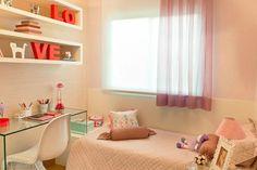 Projetada pelas arquitetas Helaine Pinterich e Ester Kloss, este quarto recebeu um papel de parede listrado, cama box, bancada feita inteiramente de vidro para estudos e uma cadeira Panton branca.
