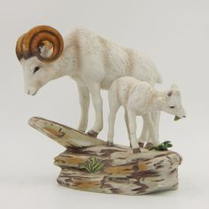 SOLD - Vintage pre-owned decorative collectible HOMCO mountain goat figurine.  The bisque porcelain ceramic figurine features a white ram mountain goat with curved horns standing beside a white baby goat on a rocky base.  The baby goat is eating a plant and has two black nubs for horns.