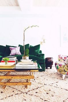 Luxe living room with velvet green couch, gold coffee table and printed chair.