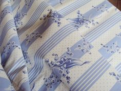 A lovely Piece of Vintage French Cotton Fabric.    The design is blue and white stripes with sprays of lily of the valley in blue. This has