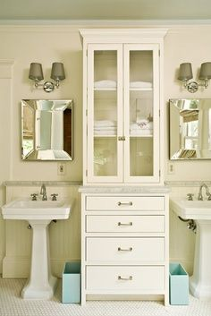 Pedestal sinks with storage in between.
