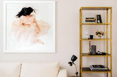 Pale pink walls in living room with oversized artwork, neutral sofa, and tall bookshelf
