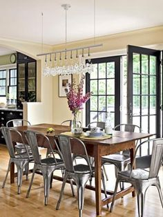 Shiny steel café chairs from Sundance cozy up to a rustic Peruvian trestle table. The modern chandelier is from Design Within Reach.  Read more: New Hampshire Farmhouse Design - Decor of a New Hampshire Farmhouse - Country Living