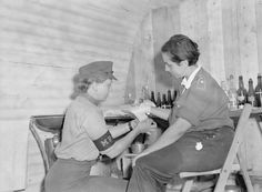 Lance Corporal Jean Burck of New Malden, Surrey, applies first aid treatment to a prisoner at a camp for SS, Luftwaffe and civilian women prisoners of war at Vilvoorde on the outskirts of Brussels.