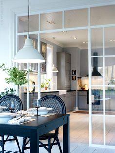 Verrière blanche qui offre une transition entre le salon et la cuisine