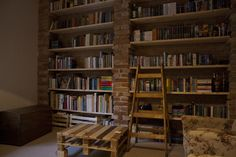 Rustic home, combining old and pallet furniture. Bookshelves made out of bricks and floorboards.