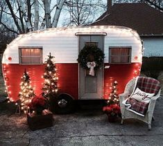 A red and white vintage camper is charming lit up at night, decorated for Christmas. #vintagecamper #holidaydecor #Christmasdecor
