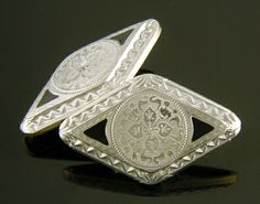 """The elegant contrast of richly engraved platinum and black enamel accents is heightened by the dramatic navette shape and Art Deco zigzag borders. These cufflinks bespeak the exuberant elegance of the 1920s. Just right for """"putting on the Ritz"""" at Jay Gatsby's next black tie affair. Created in platinum and 14kt gold, circa 1925."""