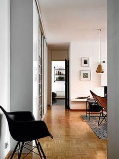 Eteisestä näkee läpi asunnon keittiöön saakka. Kirjahyllyt on piilotettu liukuovien taakse.