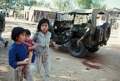 30 Jan 1968, Da Nang, South Vietnam --- 1/30/1968-Da Nang, South Vietnam- Two young girls, one carryng an infant, run past a Jeep where a South Vietnamese soldier is slumped as street fighting continues between Allied and Viet Cong forces. --- Image by © Bettmann/CORBIS