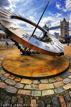 """Point the way - Tower Bridge is seen beyond the large Sundial Statue in London along the Thames. This is a hand held hdr. I had to hand hold it since I was too lazy to carry my tripod around on this particular day and the security guards get after you if you use one here. The newer cameras are fast enough and the alignment routines are good enough to do a reasonable job, even in fairly low light situations."" J. Neeley"