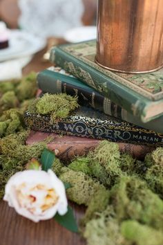 Books stacked, greenery (not moss) around them with flowers on top, then table numbered book to the side #moss