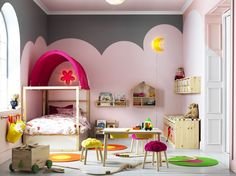 A large children's bedroom furnished with a pine bed with posts and a pink canopy. Shown together with a pine table that has two storage boxes under the table top and a storage bench with plastic boxes in white and pink.