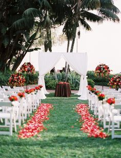 Bright red blooms and crisp white chairs popped against a grass aisle at this outdoor @Mandy Dewey Seasons Resort The Biltmore Santa Barbara wedding ceremony.