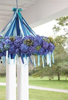 "Hang a colorful candelabrum in the porch entryway to welcome guests. Cover a wreath frame with blue ""Dutch"" hydranges, then use five coordinating shades of ribbon to suspend from a sturdy hook."
