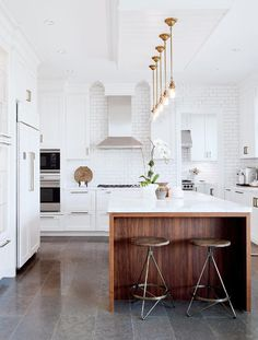 white cabinets + white subway tile + walnut + gold pendants