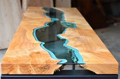 houten-tafel-glas-7. Meubelmaker Greg Klassen vind inspiratie in zijn landschap en vertaalt dat in zijn werk. Zijn River Collection is een serie van handgemaakte tafels die elke voorzien zijn van rivieren van blauwachtig-groen glas. De one-of-a-kind tafels bestaan meestal uit twee ongelijke stukken hout die verbonden worden door het speciaal geslepen glas. Klassen gebruikt bomen uit de buurt die duurzaam geoogst zijn aan de oevers van de rivier.