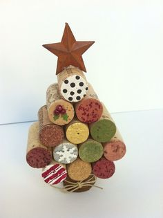 Darling Christmas tree crafted using wine corks. It is decorated on both sides with acrylic paints and small craft items. It is topped with a rusty tin star. At the base a twine bow is wrapped around the brown raffia covered wood dowel. I used 13 corks and it stands 6 from bottom to tip of star.