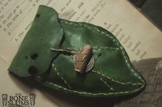 This gorgeous rune set comes in a vibrant green scrap leather pouch, distressed by hand to look as though a caterpillar made a meal of it. The leaf veins are hand stitched and the pouch ties with a single piece of hemp that wraps around a small wood bead that has small carved 'worm holes'. The ru...