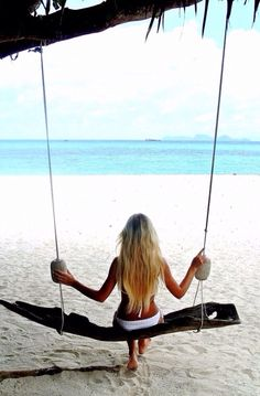 Girl sitting on a swing tied to a tree on a white Sand Beach