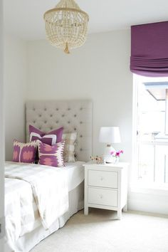 Chic tan and purple girl's room boasting a tufted headboard on twin bed dressed in white and tan striped duvet, tan gingham pillow and purple pillows next to a single nightstand illuminated by a window dressed in a purple roman shade as well as a cream beaded chandelier, PB Teen Catalina Beaded Chandelier.