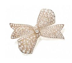 DIAMOND BOW BROOCH, CIRCA 1900.  The pierced ribbon bow set in the center with an old European-cut diamond weighing approximately .80 carat, completed by 200 smaller old European-cut, old-mine and rose-cut diamonds weighing approximately 20.00 carats, mounted in gold and silver.